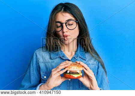 Young caucasian woman eating a tasty classic burger making fish face with mouth and squinting eyes, crazy and comical.
