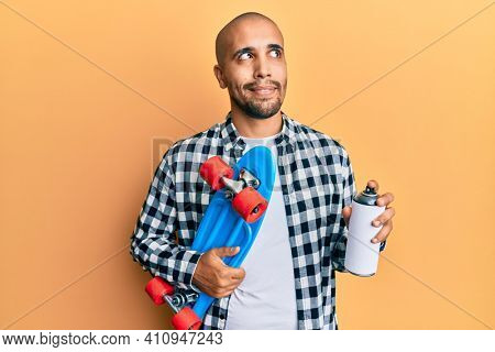 Hispanic adult skater man holding skate and graffiti spray smiling looking to the side and staring away thinking.