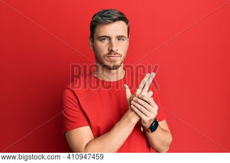 Handsome caucasian man wearing casual red tshirt holding symbolic gun with hand gesture, playing killing shooting weapons, angry face