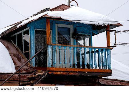 Bashkiria, Russia - 01.30.2021: Old Decrepit Open Balcony In The Russian Village. Blurry Winter Skie