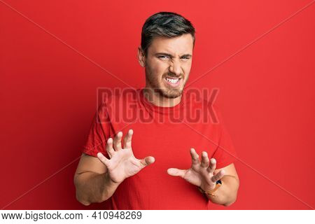 Handsome caucasian man wearing casual red tshirt disgusted expression, displeased and fearful doing disgust face because aversion reaction.