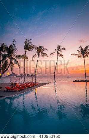 Luxury Sunset Over Infinity Pool In A Summer Beachfront Hotel Resort At Tropical Landscape. Tranquil