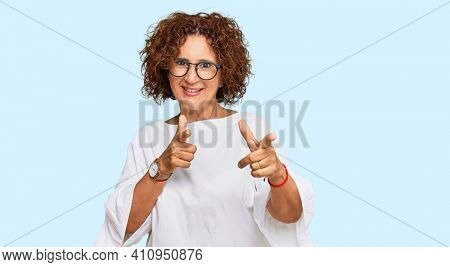 Beautiful middle age mature woman wearing casual clothes and glasses pointing fingers to camera with happy and funny face. good energy and vibes.