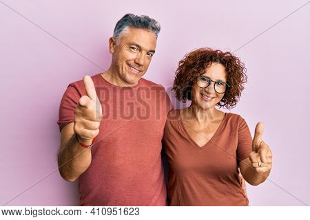 Beautiful middle age couple together wearing casual clothes pointing fingers to camera with happy and funny face. good energy and vibes.