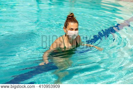 Young Woman In Medical Mask In Outdoor Swimming Pool With Garden Background Tourists Fear The 2020-n