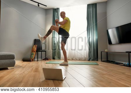 Coach Lifting Leg And Doing The Exercising At Home. Trainer In Sportswear Standing Near A Sports Mat