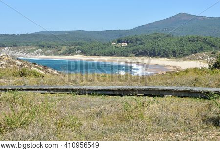 Beach With Wooden Boardwalk, Waves Breaking, Forest And Blue Sky At Rias Baixas Region. Porto Do Son