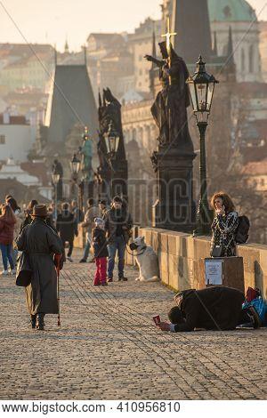 Prague, Czech Republic. 03-02-2021. Beggar Asking For Money On The Charles Bridge In The City Center