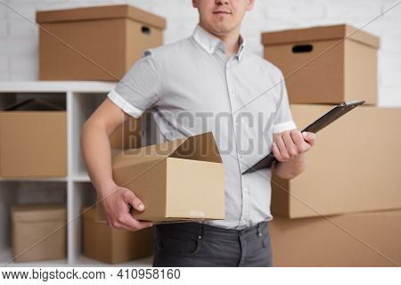 Business And Work Concept - Close Up Of Postman Or Loader In Warehouse Standing With Box And Clipboa