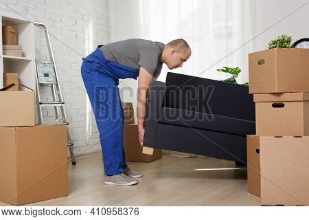 Moving Day Concept - Man Loader Lifting Sofa In Apartment
