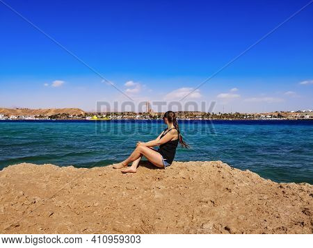 Barefoot Young Woman With Blond Braided Hair Sits On A Rock Against The Background Of The Sea Panora