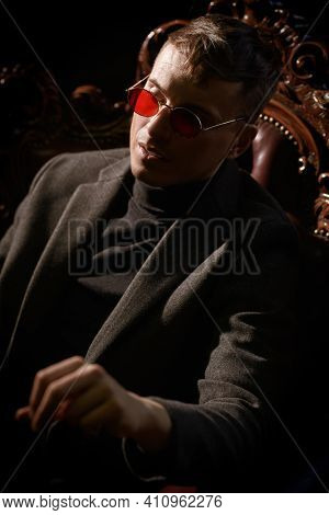 Imperious mature man in stylish expensive clothes and glasses sits in the armchair in the luxury vintage apartment. Mafia, gangster man.