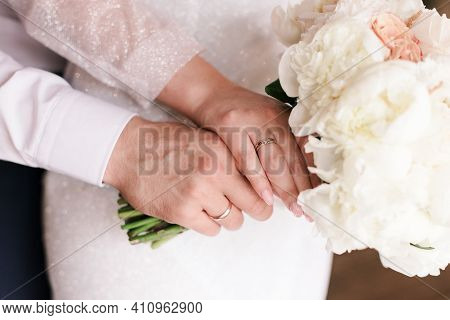 The Bride And Groom Decorate The Wedding Bouquet