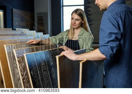 Young Couple Choosing Wood Texture Laminate Floor From Samples In Flooring Store For House Improveme