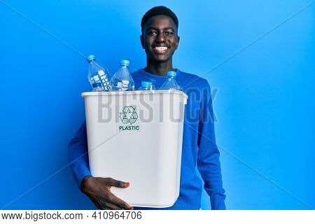 Young african american man holding recycling wastebasket with plastic bottles looking positive and happy standing and smiling with a confident smile showing teeth
