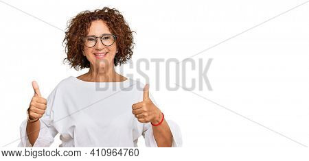 Beautiful middle age mature woman wearing casual clothes and glasses success sign doing positive gesture with hand, thumbs up smiling and happy. cheerful expression and winner gesture.