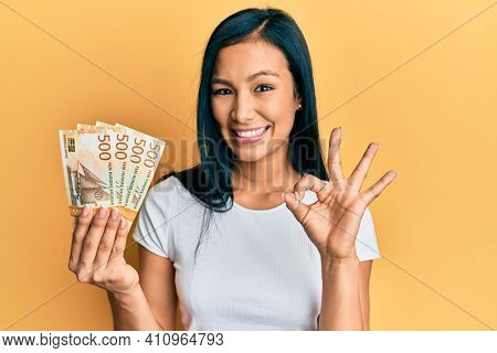 Beautiful hispanic woman holding 500 norwegian krone banknotes doing ok sign with fingers, smiling friendly gesturing excellent symbol