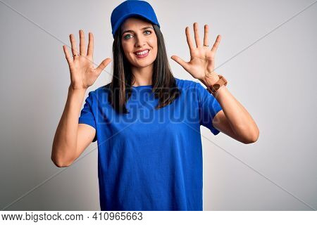 Young delivery woman with blue eyes wearing cap standing over blue background showing and pointing up with fingers number ten while smiling confident and happy.