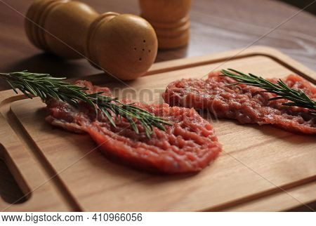 Raw Piece Of Pork Chop With Seasonings And A Sprig Of Rosemary On A Wooden Board