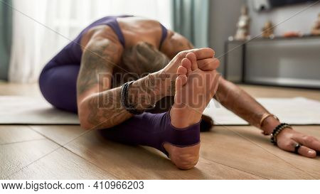 Athletic Woman In Tight Sportswear Practicing Yoga, Doing Head To Knee Pose. She Is Touching Toes, S