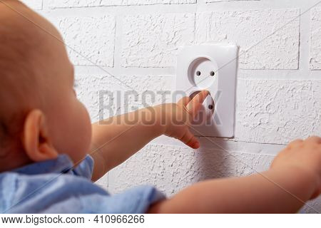 Unrecognizable Caucasian Boy Is Playing With Open Electrical Outlet. Baby Wires. Dangerous Games Wit