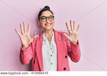 Beautiful middle eastern woman wearing business jacket and glasses showing and pointing up with fingers number ten while smiling confident and happy.