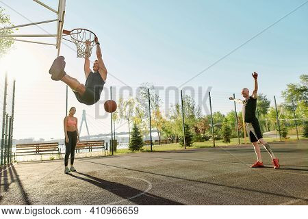 Skilled Guy Throwing Ball Into Basket, While Playing Basketball. Full Length Shot Of Active Young Pe