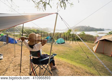 Asian Female Tourists Sit On Camping Chairs, Relax And Have Fun, Camping With Mountain And River Vie