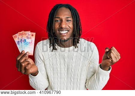 African american man with braids holding 20 swiss franc banknotes screaming proud, celebrating victory and success very excited with raised arm