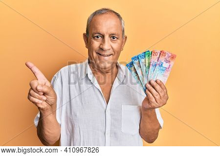 Handsome mature senior man holding swiss franc banknotes smiling happy pointing with hand and finger to the side