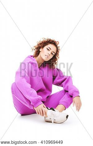 Young girl model posing in a bright sportswear and sneakers on a white background. Sportswear fashion. Studio shot.