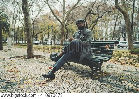 A Dapper Stately Black Senior In An Elegant Custom Suit Is Sitting On A Street Bench In An Autumn Pa