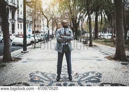 A Stately Mature Hairless Barbate Black Man Entrepreneur In A Dapper Custom Made Suit Is Standing Wi