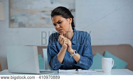 Displeased Freelancer Sitting With Clenched Hands And Looking At Laptop