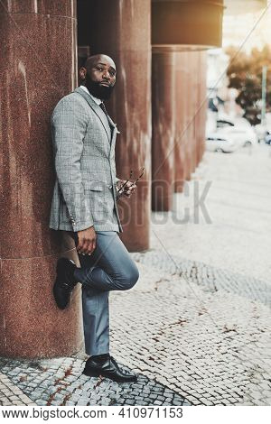 Vertical Shot Of An Elegant Bearded Bald Black Businessman In A Fashionable Suit, Standing On The St