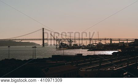 Sunset In Lisbon, Portugal: Silhouettes Of The Bridge 25 De Abril And Docks In The Background, Roofs