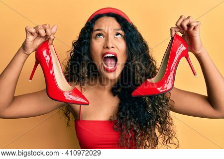 Young latin woman holding red high heel shoes angry and mad screaming frustrated and furious, shouting with anger looking up.