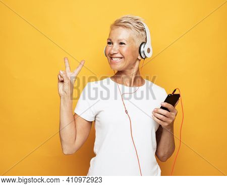 woman with short white hair wearing white tshirt listening to music with headphones and show victory sign over yellow background