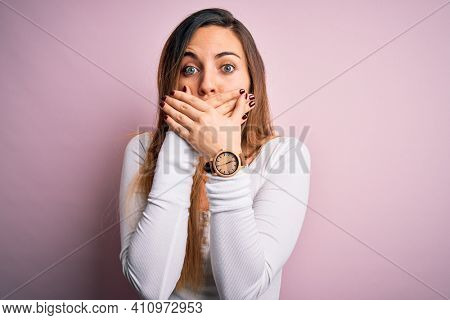 Young beautiful blonde woman with blue eyes wearing white t-shirt over pink background shocked covering mouth with hands for mistake. Secret concept.