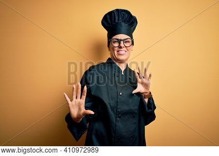 Young beautiful brunette chef woman wearing cooker uniform and hat over yellow background disgusted expression, displeased and fearful doing disgust face because aversion reaction. With hands raised