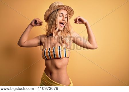 Young beautiful blonde woman on vacation wearing bikini and hat over yellow background showing arms muscles smiling proud. Fitness concept.