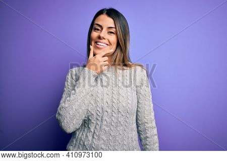 Young beautiful woman wearing casual sweater standing over isolated purple background looking confident at the camera smiling with crossed arms and hand raised on chin. Thinking positive.