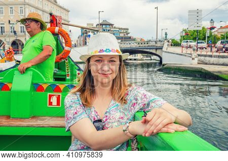 Aveiro, Portugal, June 13, 2017: Young Beautiful Woman Traveler With Hat Sailing In Moliceiro Tradit