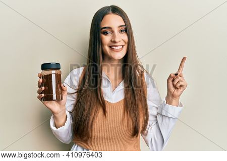 Beautiful brunette young woman holding soluble coffee smiling happy pointing with hand and finger to the side