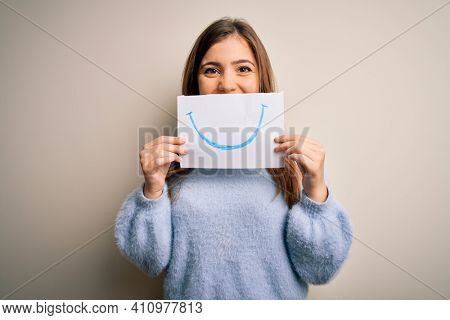 Young blonde woman holding funny smile drawing on mouth as happy expression with a happy face standing and smiling with a confident smile showing teeth