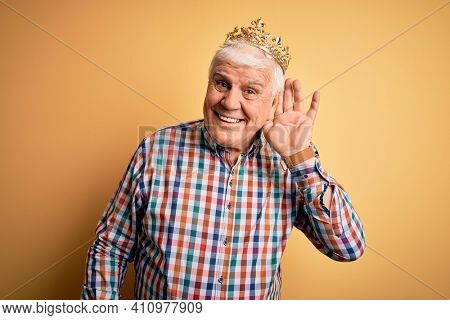 Senior handsome hoary man wearing golden crown of king over isolated yellow background smiling with hand over ear listening an hearing to rumor or gossip. Deafness concept.