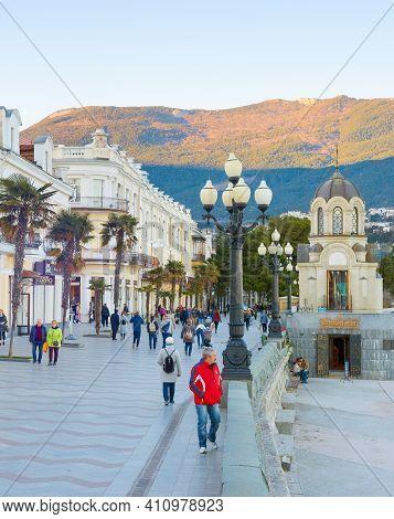 Yalta, Crimea - April 3, 2018: People Walking By Resort City Embankment, Mountain In Sunset Light In