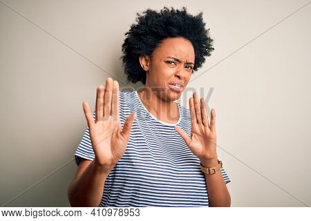 Young beautiful African American afro woman with curly hair wearing striped t-shirt disgusted expression, displeased and fearful doing disgust face because aversion reaction. With hands raised