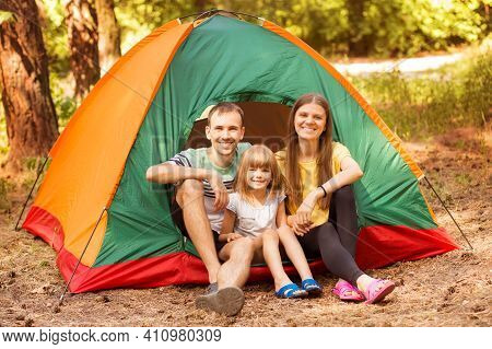 Family Of Three People Camping And Having Fun Time Together In Summer Forest. Camping Holidays.