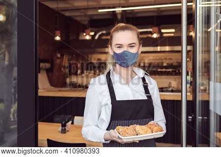 Small Business Owner Smiling And Standing At Entrance Of Open Restaurant While Reopening After Lockd